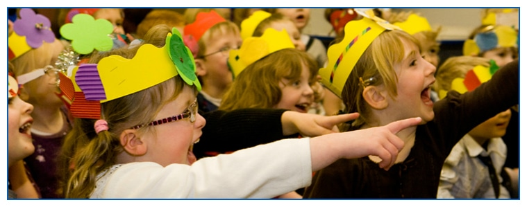 Image of children laughing and pointing at children's entertainers performing a magic show at a children's party